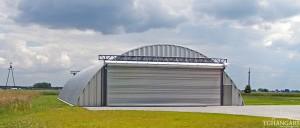 Lekkie samonośne hangary łukowe (arch prefabricated building) z alucynku - hangar lotniczy postojowy TG Hangars na prywatnym lądowisku.